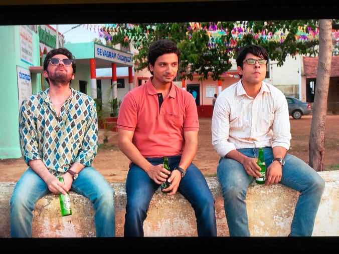 3 Indian men sit on a wall drinking beer in the movie Upstarts